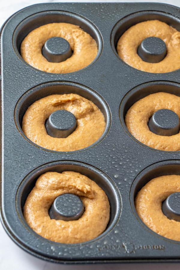 Pumpkin donut batter in the donut pan.