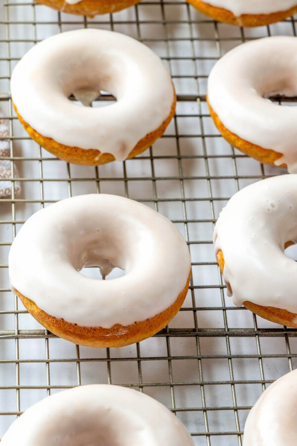 Pumpkin donuts with maple glaze on a cooling rack.