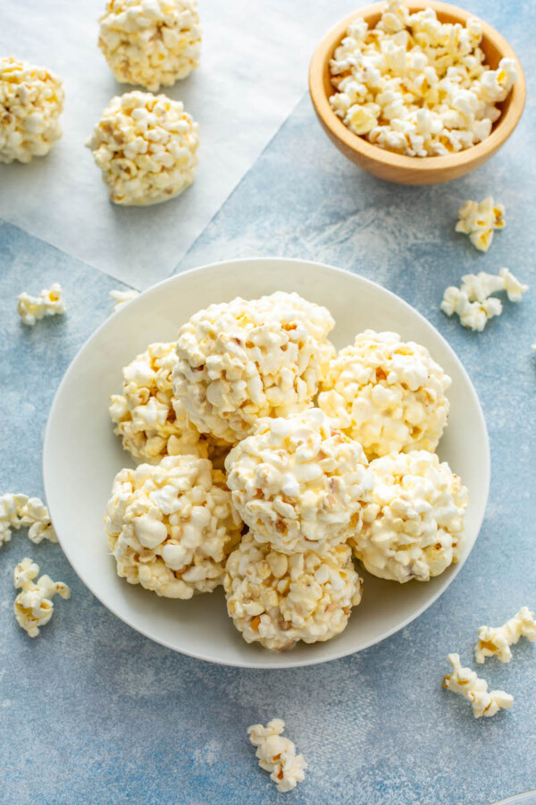 A bowl is holding several marshmallow popcorn balls with extra popcorn around the bowl.