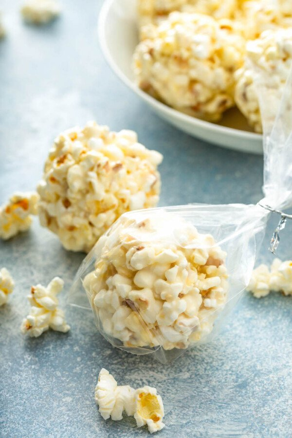 A popcorn ball is wrapped in plastic wrap