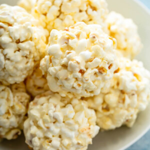 A plate is holding a pile of marshmallow popcorn balls