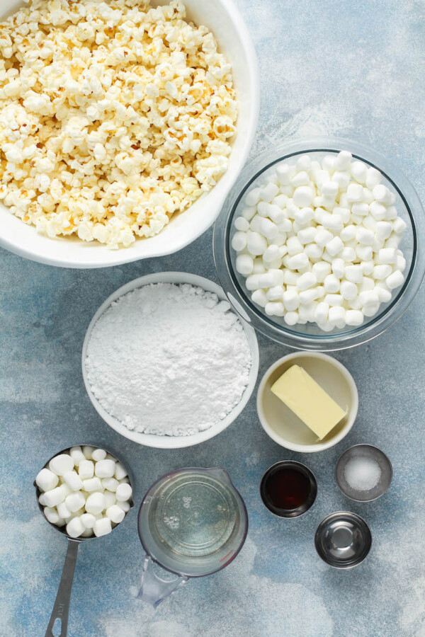 The ingredients for marshmallow popcorn treats are placed on a white tabletop