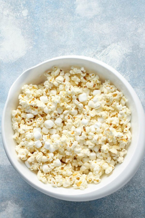 A bowl of popped popcorn is sitting on a white tabletop