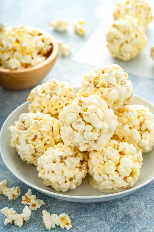 A pile of marshmallow popcorn balls is on a white plate