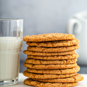 Stack of molasses cookies next to a glass of milk.
