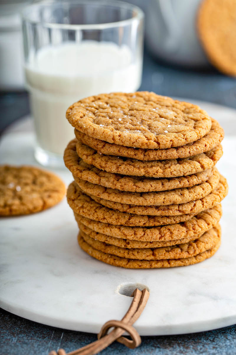 Stack of molasses cookies with a glass of milk.