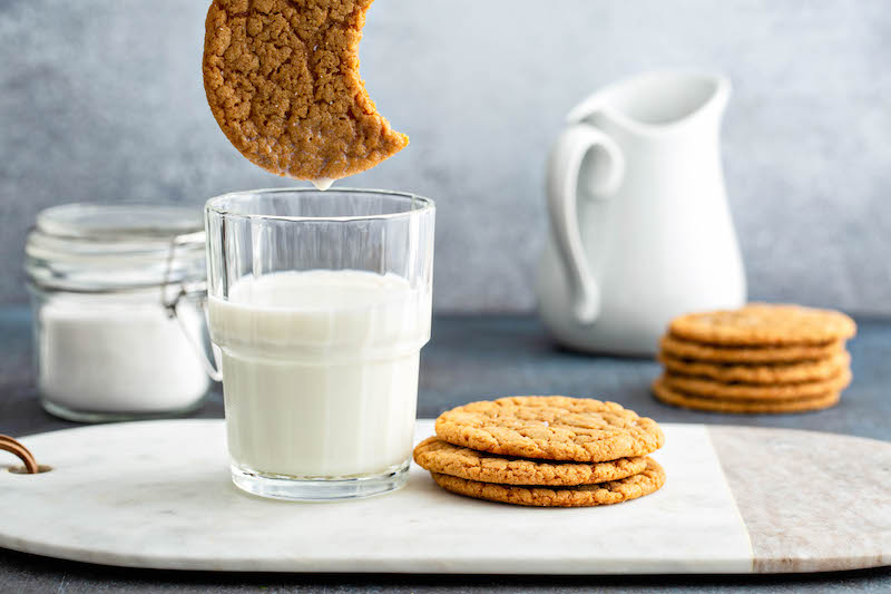 Molasses cookie with a bite taken out of it, over a glass of milk.