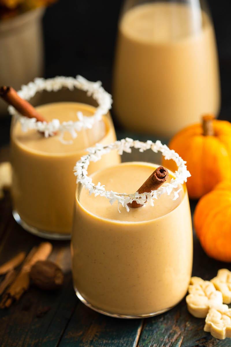 Glasses of pumpkin coquito with cinnamon sticks.