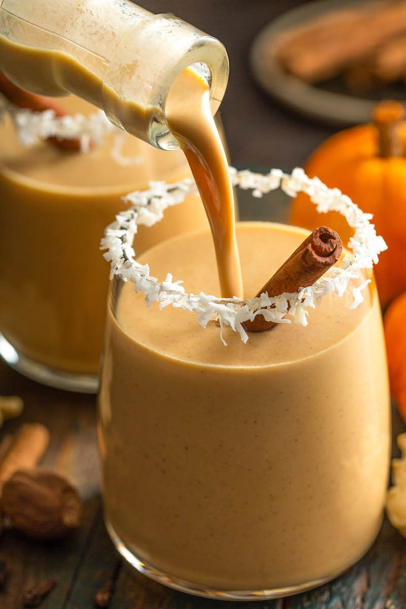 A glass of pumpkin coquito being poured, with a cinnamon stick.