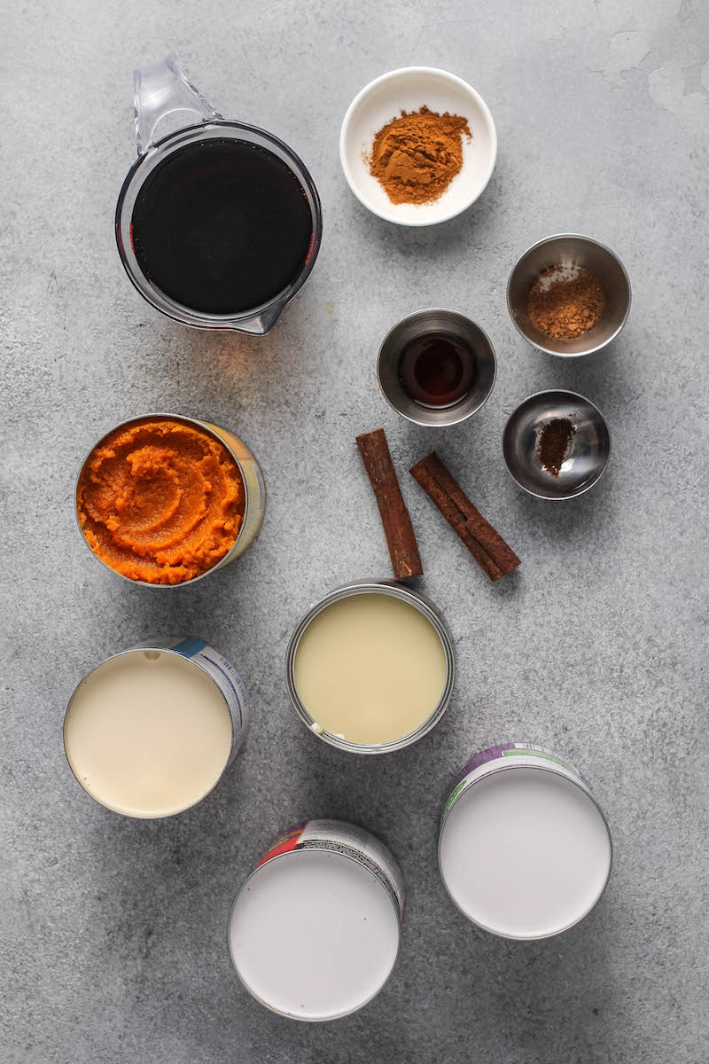 Ingredients for pumpkin coquito in measuring cups and bowls.