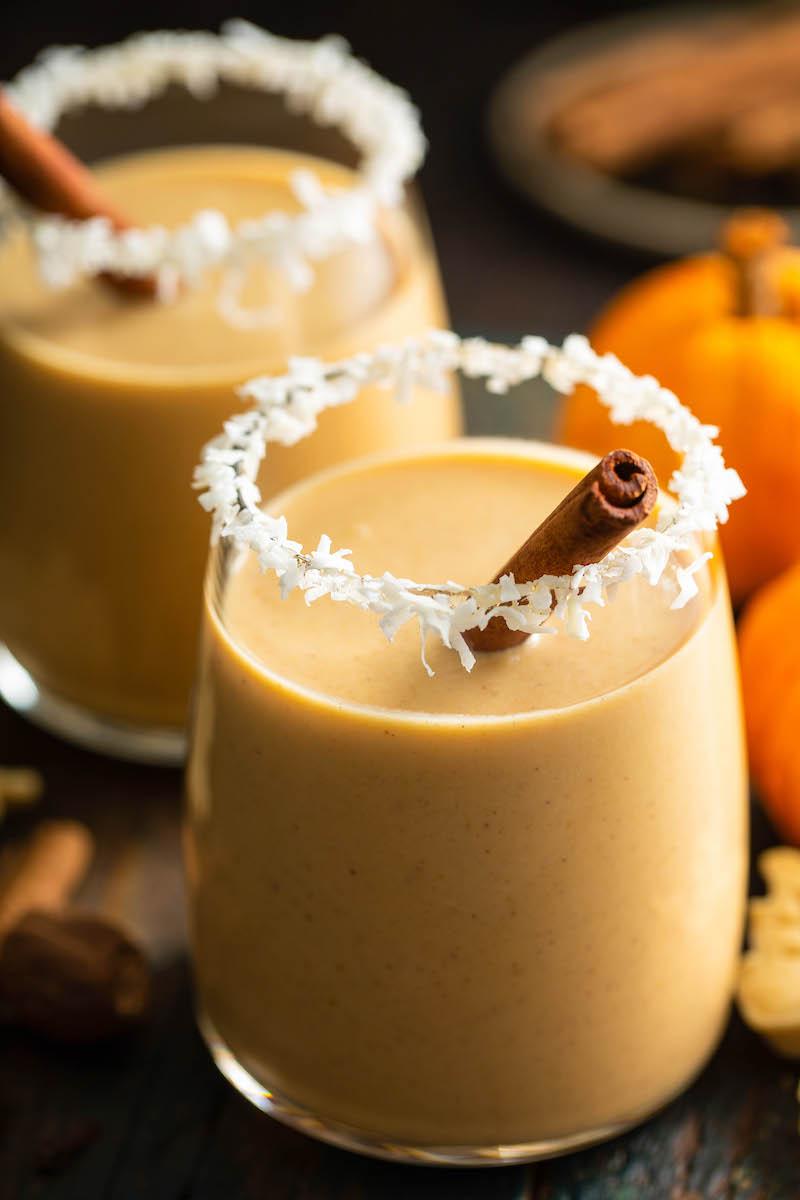 2 glasses of pumpkin coquito with cinnamon sticks.