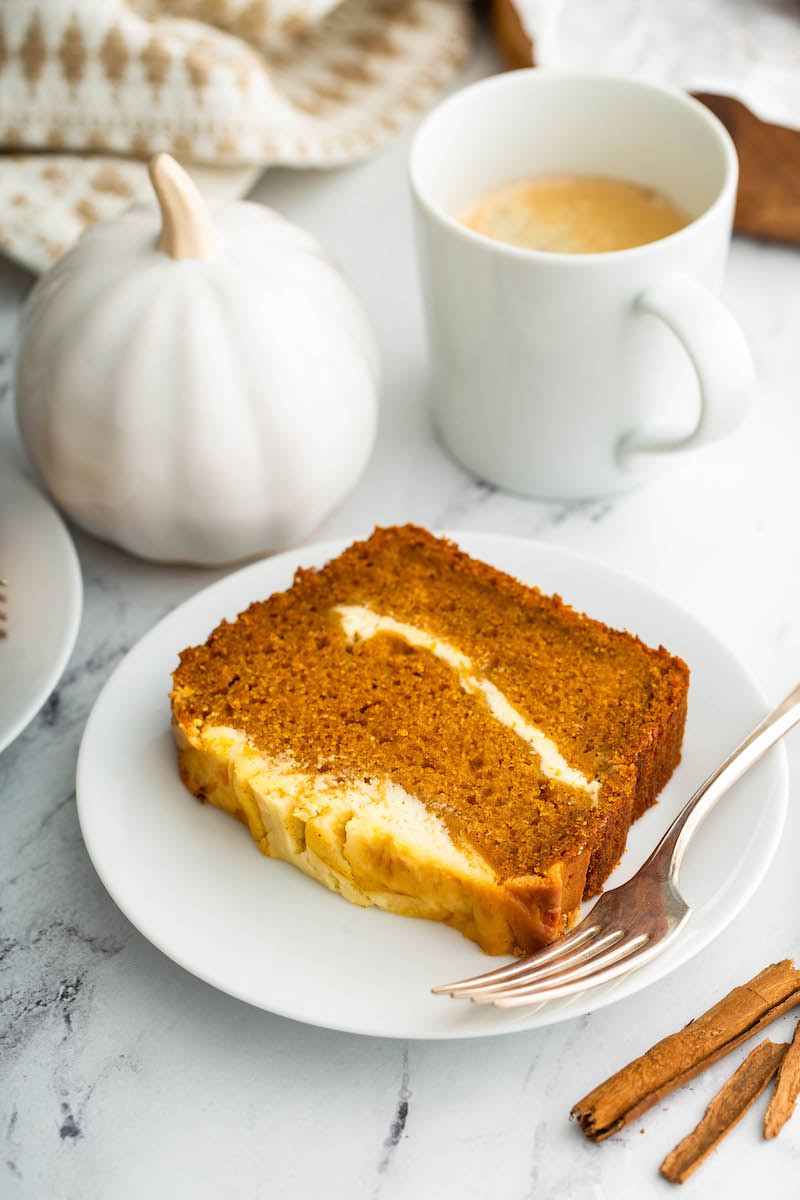 Slice of pumpkin cream cheese bread on a plate with a fork.