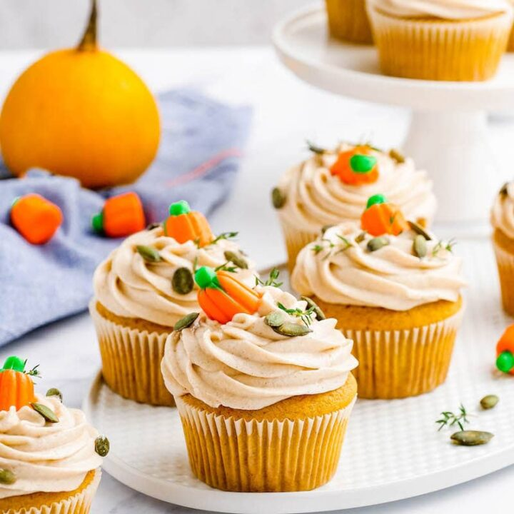 Pumpkin cupcakes with frosting and candy pumpkins on top.