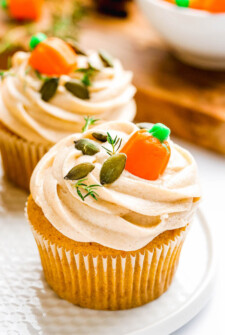 Pumpkin cupcakes with frosting and fall decorations on top.