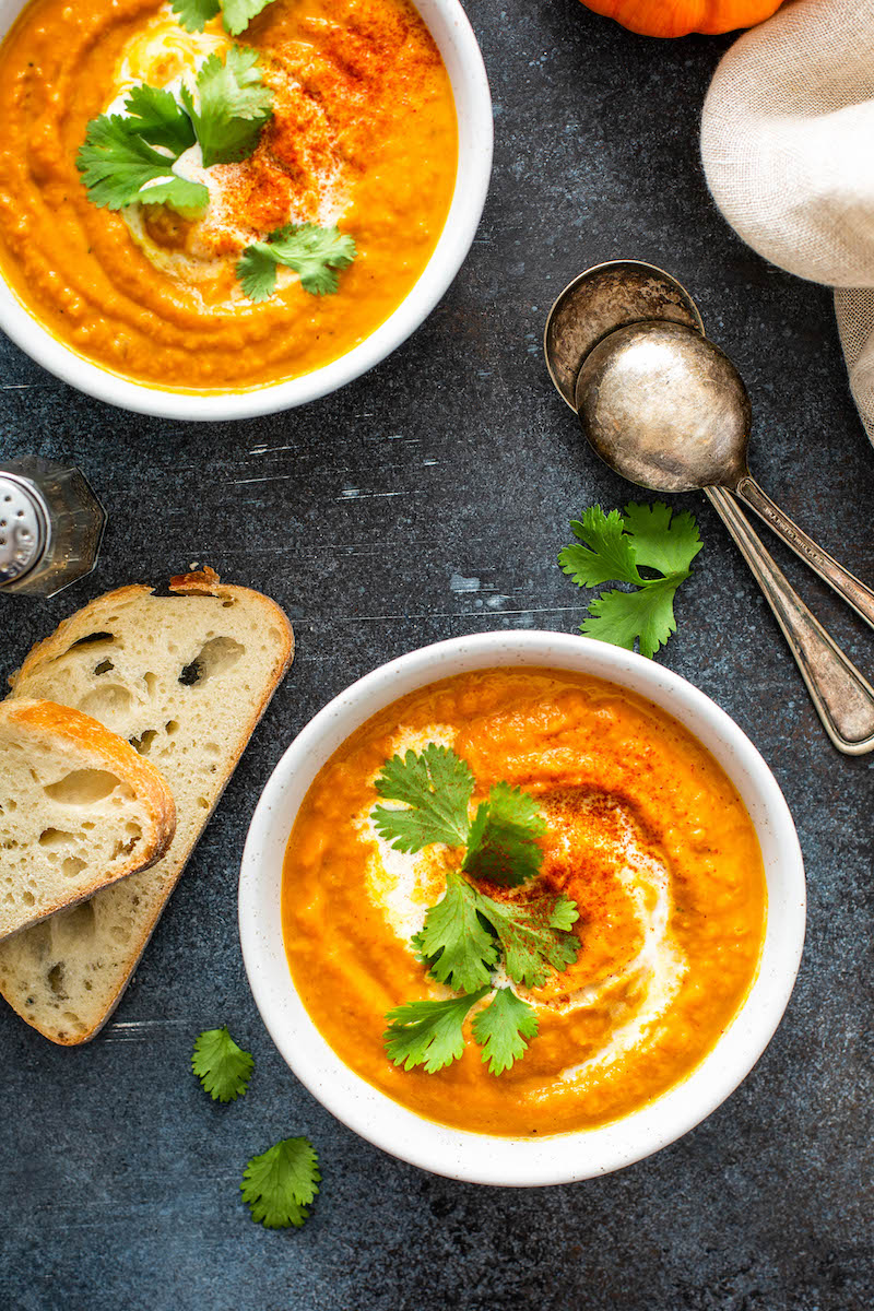 Two bowls of pumpkin soup with bread.