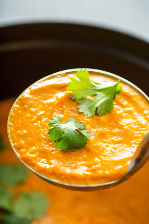 Ladle full of pumpkin soup with cilantro.