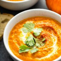 Bowl of pumpkin soup with chopped cilantro.