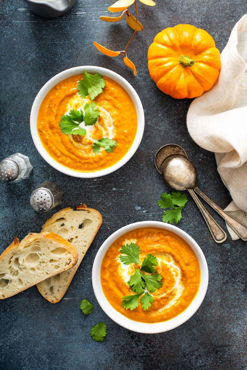 Two bowls of pumpkin soup with bread slices.