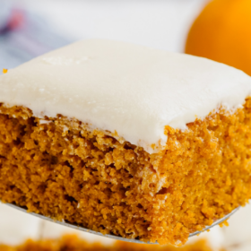 Pumpkin bar on a spatula with cream cheese on top.