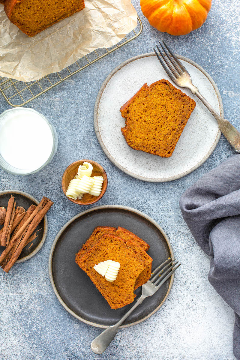 Pumpkin loaf on a grey and white plate with forks and butter.