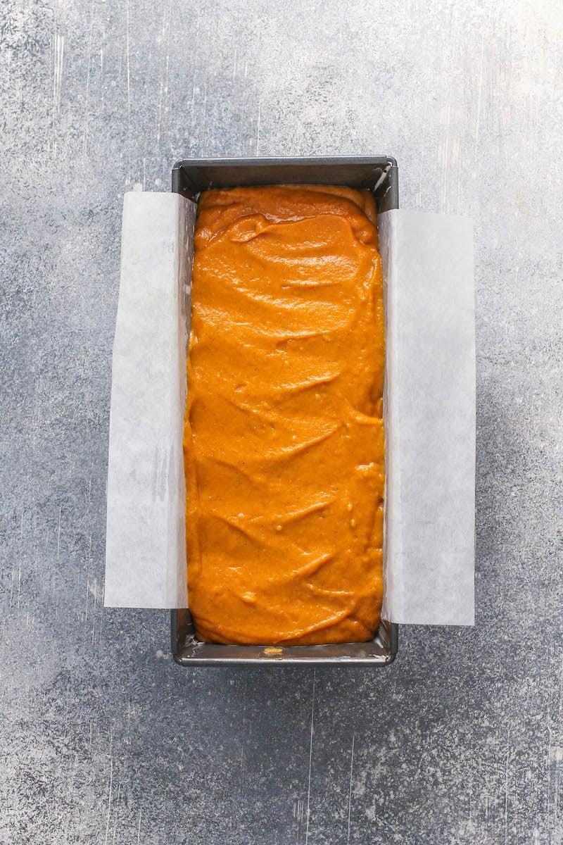 Unbaked pumpkin bread batter in a lined loaf pan