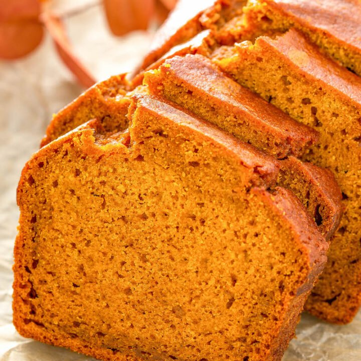 Up close image of pumpkin bread sliced on a piece of parchment paper.