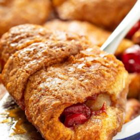 Easy Cranberry Apple Dumplings on a spatula being pulled out of a baking dish.