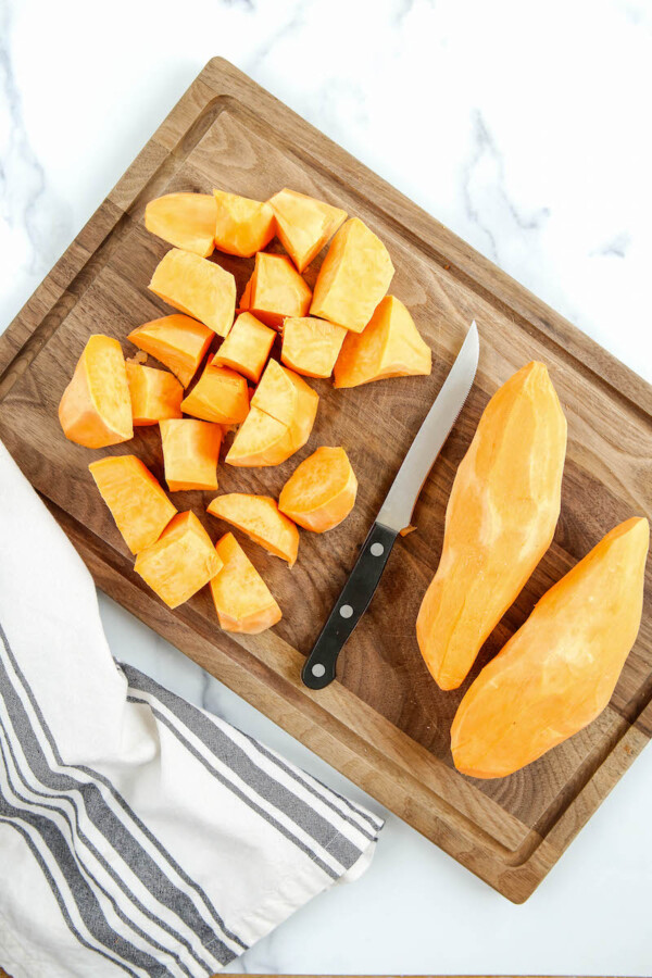 Chopped sweet potatoes with a knife.