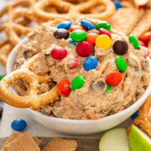 A bowl of monster cookie dough dip is on a counter with a pretzel being dipped into it