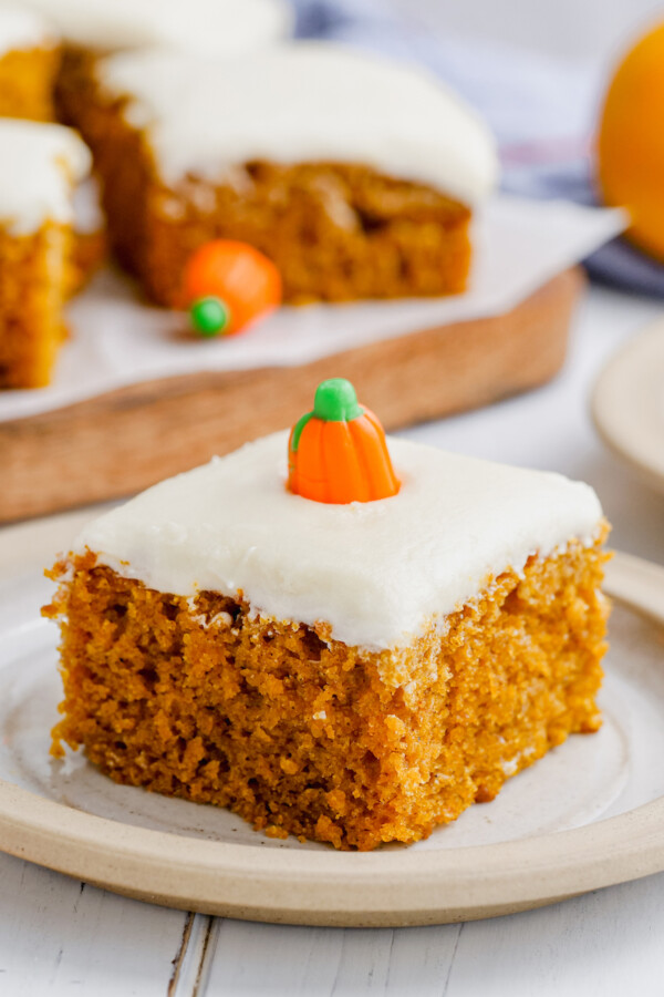 A pumpkin bar is on a plate with a candy pumpkin on top