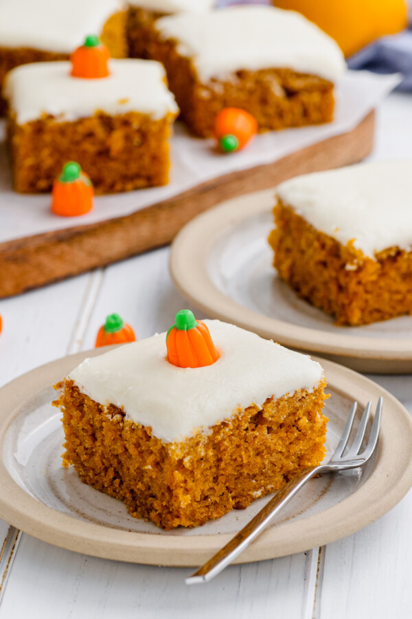 Slices of pumpkin bars are topped with candy orange pumpkins