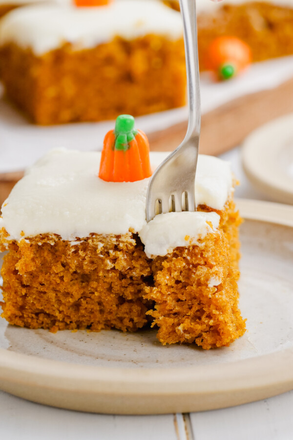 A forkful is being taken out of a pumpkin cake with icing on top.