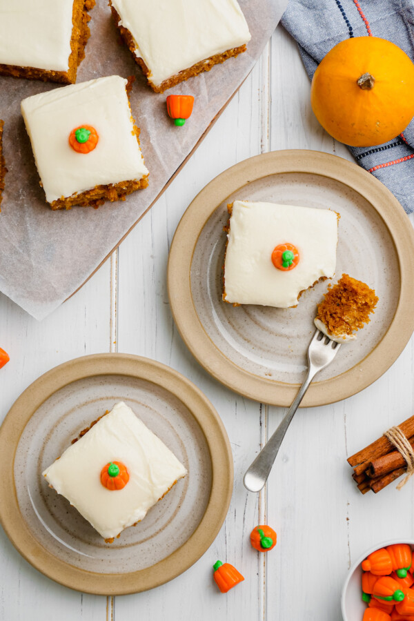 Two pumpkin bars are plated on a white surface