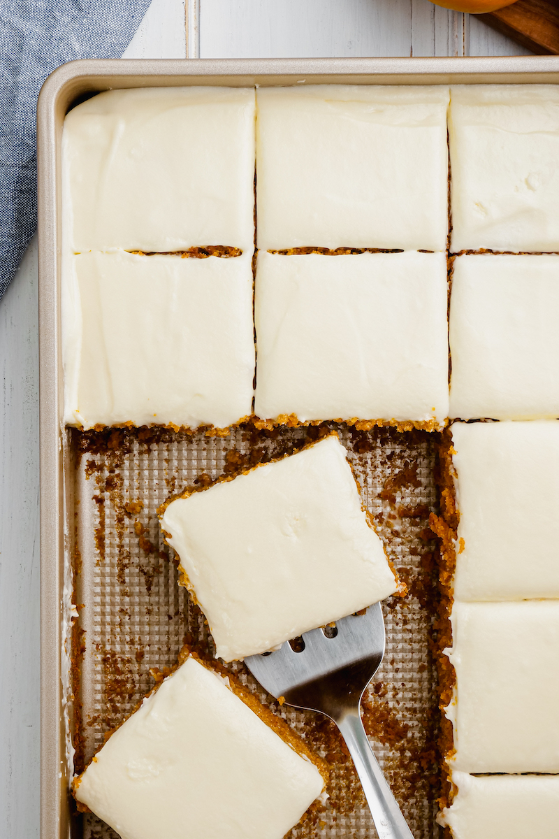 Slices of dessert bars are in a pan with one on a spatula.