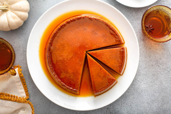 Two slices of pumpkin flan are being sliced out of the dessert
