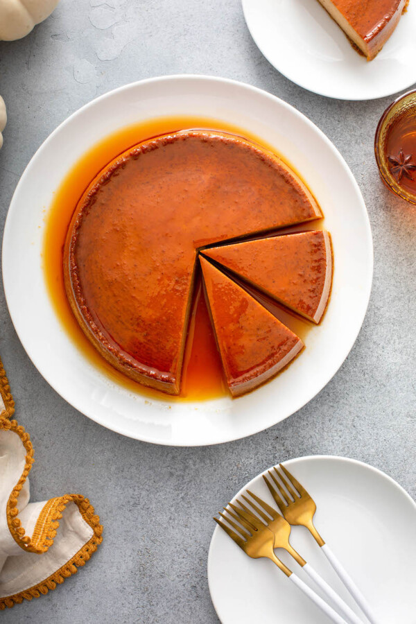 Two slices of pumpkin flan are cut out of the cake