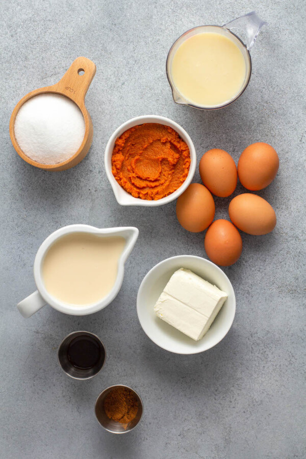 The ingredients for pumpkin flan are spread out on a gray surface