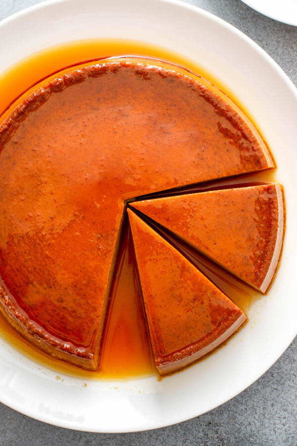 Two slices of pumpkin flan are being sliced into
