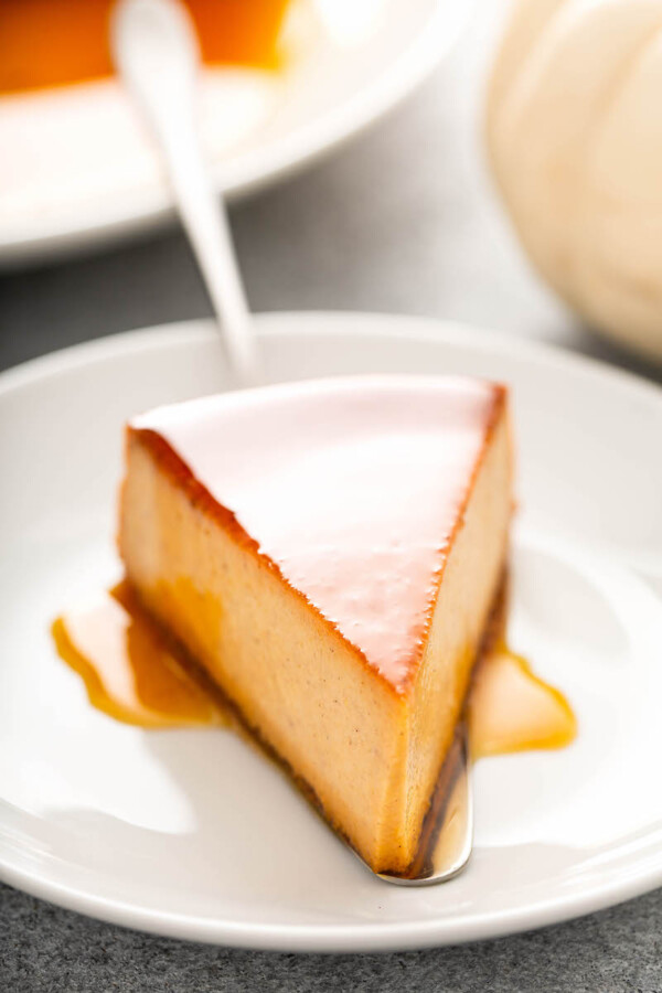 A piece of pumpkin flan is placed onto a white plate