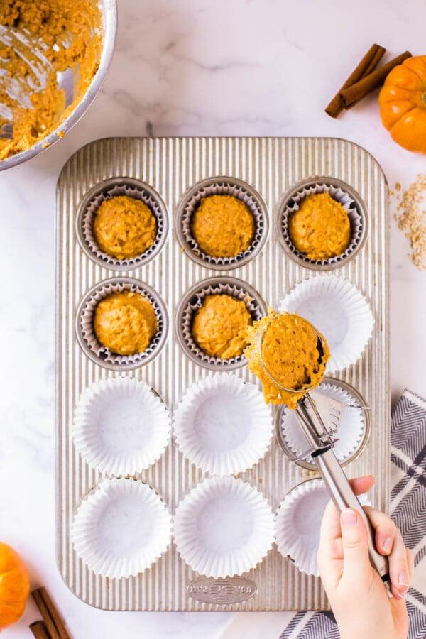 Pumpkin muffin batter in a muffin tin.