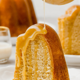 Rumchata pound cake on a white plate with RumChata sauce being poured on top.