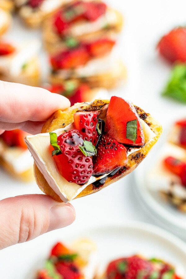 Crostini being held by a hand with strawberries, brie and balsamic vinegar drizzled on top.