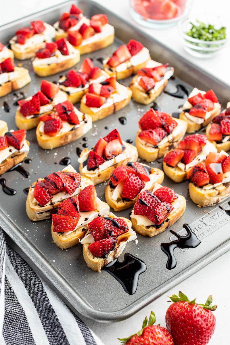 Pan of strawberry brie crostini with balsamic glaze.