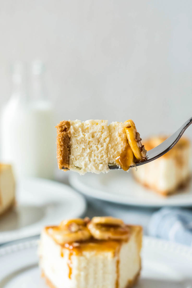 Bite of bananas foster cheesecake on a fork.