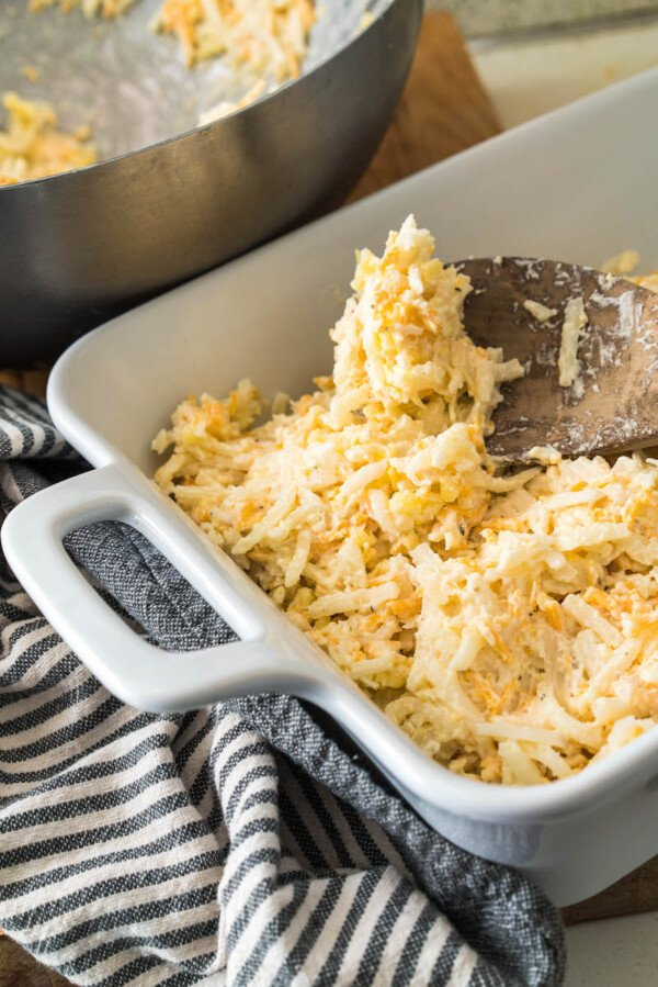 Unbaked potato casserole with shredded cheese.