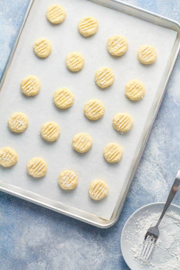 Coconut Whipped Shortbread Cookie dough is placed on a prepared baking sheet.