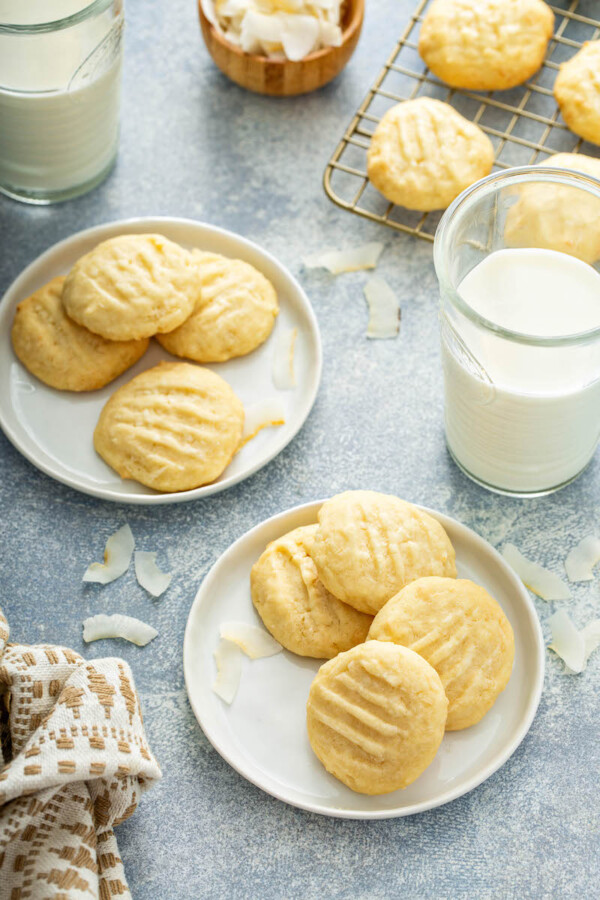 Two white plates have several cookies on top of them with a glass of milk nearby.