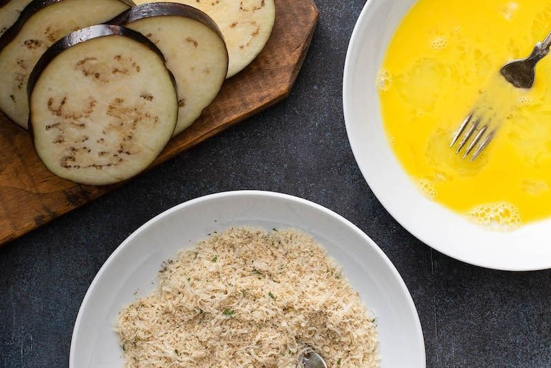Sliced eggplant, breadcrumbs and egg wash in a bowl