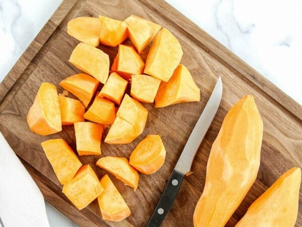 Peeled diced sweet potatoes on a cutting board