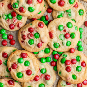Overhead image of red and green m&M cookies on a baking sheet.